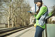 Teenage girl using smartphone at platform - UUF000194