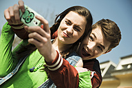 Portrait of teenage couple photographing themselves with smartphone - UUF000204