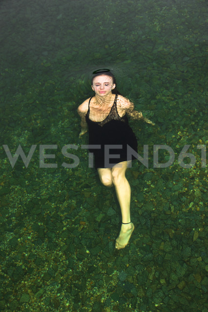 Young woman floating with evening dress in lake - FCF000013