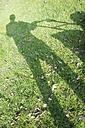 Germany, Petershagen, Shadow of a man mowing lawn - HAWF000084