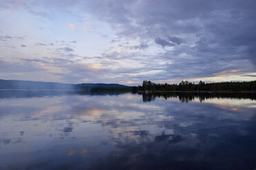 Sweden, Stroemsund, Sunset at a lake and smoke from a campfire - BR000428