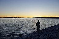 Sweden, Storuman, Man standing at lake in sunset - BR000453