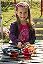 Germany, Bavaria, Landshut, Girl dyeing Easter eggs - SARF000448