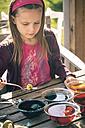 Germany, Bavaria, Landshut, Girl dyeing Easter eggs - SARF000451