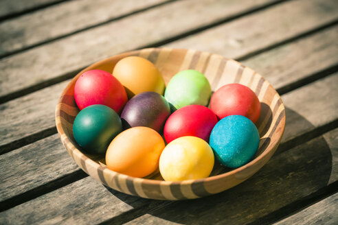 Germany, Colorful Easter eggs on wooden table - SARF000454