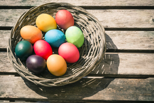 Germany, Colorful Easter eggs on wooden table - SARF000456