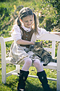 Portait of little girl sitting on wooden bench with cat - SARF000473