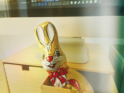 Chocolate Easter Bunny at a computer workstation look out drawer, Germany - UW000081