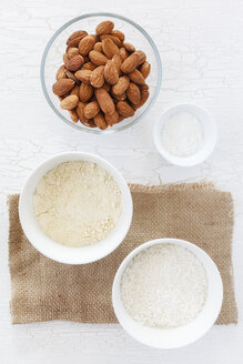 Almonds, coconut flakes and baking powder in bowls for glutenfree Carrot Coconut Banana Cupcakes - EVGF000515