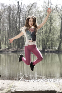Woman jumping in the air in front of water - GD000323