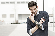 Portrait of smiling man with tattoo on his left arm - GDF000302