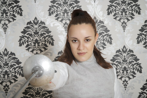 Portrait of young female fencer with floret in front of checkered wallpaper - ECF000530