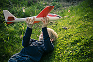 Germany, Bavaria, Landshut, Boy playing with toy aeroplane - SARF000479