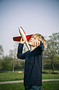 Germany, Bavaria, Landshut, Boy playing with toy aeroplane - SARF000477