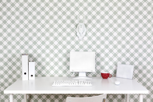 Desk at home office with white accessories in front of patterned wallpaper - DRF000643