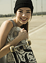Portrait of smiling young woman with skateboard - UUF000228