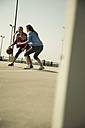 Two young women playing basketball outdoors - UUF000240