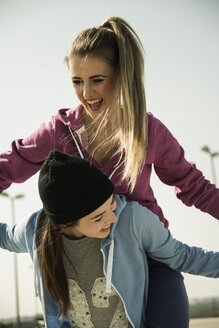 Happy young woman carrying friend piggyback - UUF000247