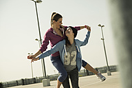 Happy young woman carrying friend piggyback - UUF000248