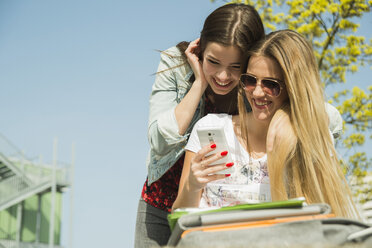 Two happy young women using cell phone outdoors - UUF000283