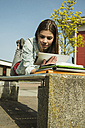 Brunette young woman lying on bench using digital tablet - UUF000301