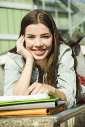 Portrait of smiling brunette young woman lying on bench - UUF000285