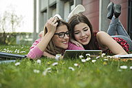 Two young women using digital tablet in meadow - UUF000296