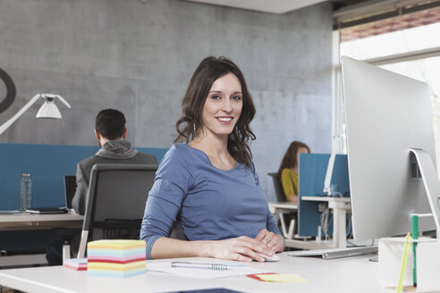 Portrait of smiling woman at his workplace in the office - RBF001619
