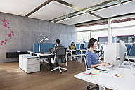 Three colleagues working in modern open space office - RBF001683