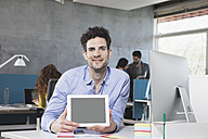 Portrait of smiling man showing tablet computer in the office - RBF001631