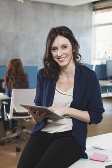 Portrait of smiling woman with digital tablet sitting at her workplace in the open space office - RBF001643