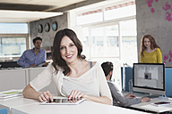 Portrait of smiling woman with digital tablet standing in an open space office - RBF001659