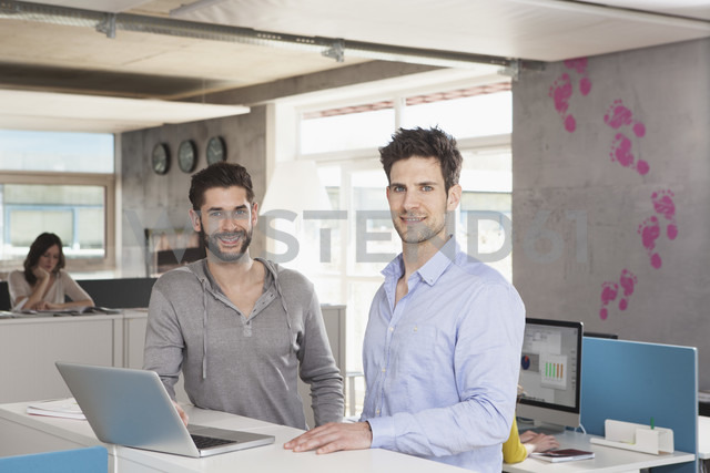 Portrait of two colleagues with laptop in an open space office - RBF001664
