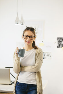 Portrait of woman with coffee cup at modern home office - EBSF000183