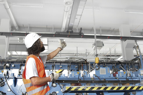 Worker with hard hat in a factory hall - SGF000579