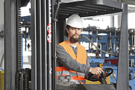 Worker with hard hat in a factory hall driving forklift - SGF000578