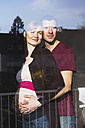 Couple expecting a baby looking out of window - MUF001473