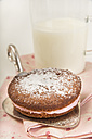 Garnished Whoopie pie on cake server in front of glass of buttermilk - CSTF000251