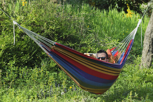 Germany, Young man lying in hammock and reading a magazine - LAF000725