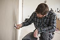 Man testing plastered wall - PA000596