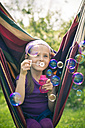 Portrait of smiling little girl blowing soap bubbles - SARF000499
