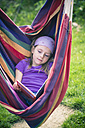 Portrait of little girl reading book in hammock - SARF000494