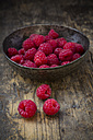 Bowl of raspberries on wooden table - LVF001064