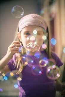 Portrait of little girl blowing soap bubbles - SARF000492