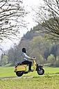 Young man driving with his Vespa on road - LAF000726