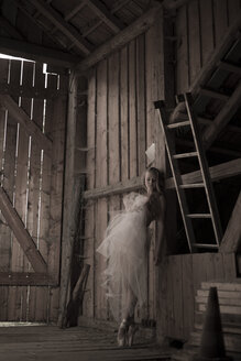 Germany, Young woman in ballet dress leaning against wall in barn - FC000040