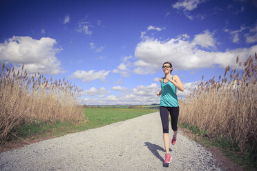 Woman jogging through the rural landscape - VTF000213