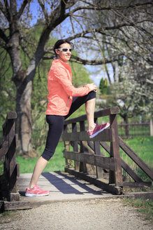 Woman stretching on a footbridge - VTF000202