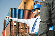 Businessman talking to teenager at container terminal - UUF000325