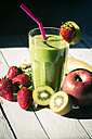 Glass of kiwifruit smoothie and fruits on wooden table - SARF000505